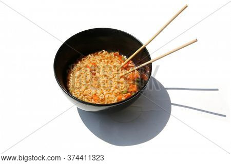 Teriyaki Beef Noodle Soup with Vegetables. Beef Noodle Soup in a Black Ceramic Bowl. Isolated on white. Room for text. Soup is enjoyed world wide for Lunch or Dinner.  Noodle Soup with Chop Sticks.