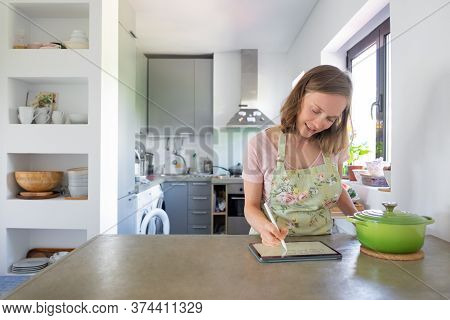 Positive Young Woman Writing Notes For Recipe On Pad Screen, Using Tablet Near Big Saucepan On Count