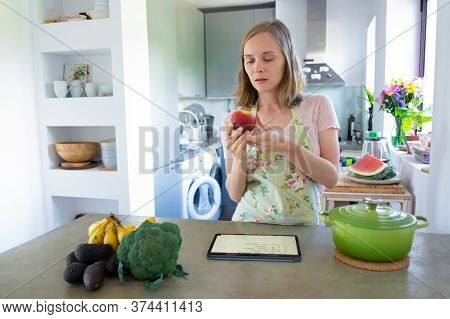 Pensive Focused Woman Holding Fruit While Cooking In Kitchen, Using Tablet Near Saucepan And Fresh V