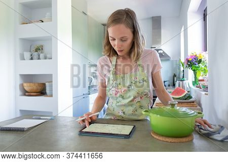 Focused Young Woman Consulting Recipe While Cooking In Her Kitchen, Using Tablet Near Big Saucepan O