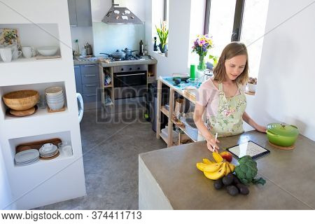 Positive Housewife Writing Notes On Pad, Consulting Recipe While Cooking In Her Kitchen, Using Table