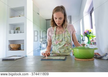 Serious Young Woman With Tablet Planning Weekly Menu, Using Digital Gadget Near Big Saucepan On Coun