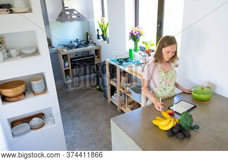Pensive Woman Consulting Recipe On Pad While Cooking In Her Kitchen, Using Tablet Near Saucepan And