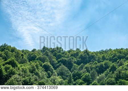 Dense Textured Clouds Over The Green Forest On The Hillside. Cloudy Day In The Green Mountains. Moun