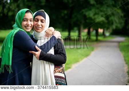 Two muslim women hugging each other in nature