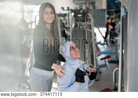Fitness trainer assisting a muslim woman in gym while using Gym Equipment