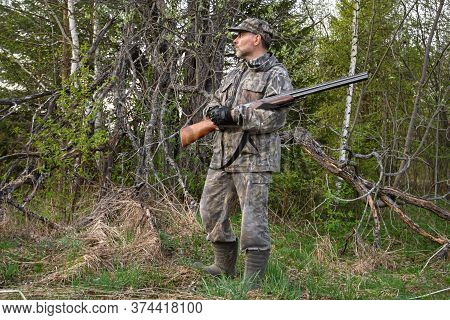 A Hunter With A Rifle In His Hands Stands In The Deciduous Forest Near A Dead Tree In The Evening