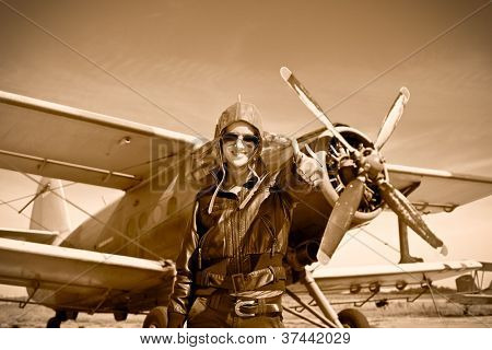 Portrait of beautiful female pilot with plane behind. Sepia photo.