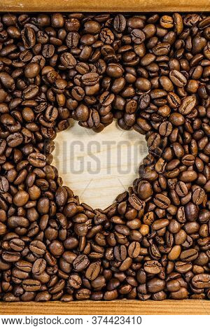 Roasted Brown Coffee Beans With Empty Heart Form Shape.