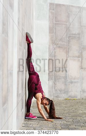 Girl Athlete Performs Gymnastic Exercise Twine Leaning On A Wall In The Fresh Air. Concept On The Th