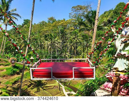 Beautiful Red Swinging Chair For Having Fun In Ubud, Bali With Trees On The Background. Bali Swing