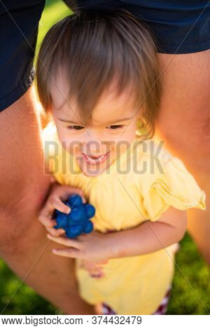 Baby Girl With With Dog Toy Laughing And Hidding Between Legs From Dog. Positive Emotions Concept. S