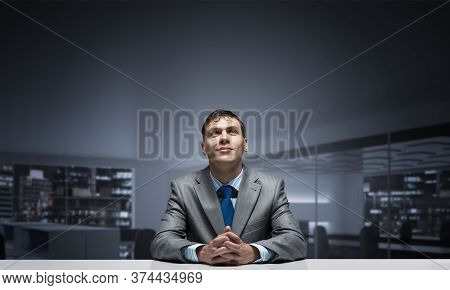 Young Smiling Man Folded Hands And Looking Upward. Happy Businessman Sitting At Desk And Dreaming Ab