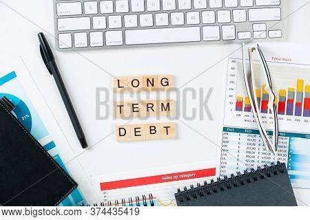 Long Term Debt Concept With Letters On Cubes. Still Life Of Office Workplace With Supplies. Flat Lay