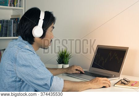 Asian Forex Trader Or Investor Or Businessman Wear Jean Shirt And Headphone Looking Forex Or Stock C