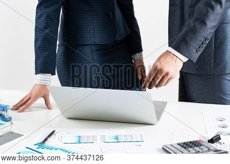 Businesspersons Stand Near Desk With Financial Charts. Manager Use Laptop Computer For Presentation.