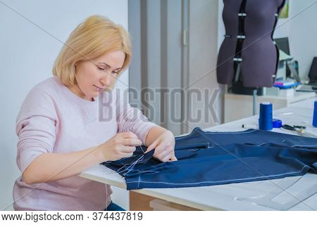 Professional Tailor, Fashion Designer Sitting And Working At Sewing Studio. Preparation Process. Fas