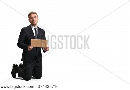 Dismissed Sad Manager Holding A Cardboard Poster On A White Background, Business Concept, Unemployme