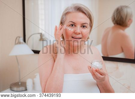 Senior Woman Anti-aging Lotion Against Dark Circles Under The Eyes. Happy Mature Woman Uses Cosmetic