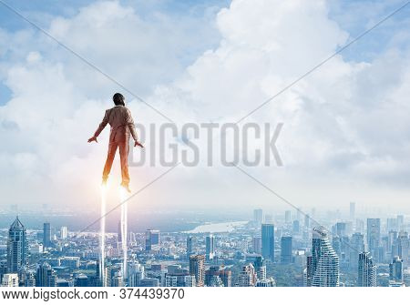 Businessman In Suit And Aviator Hat Flying In Blue Sky As Superhero. Back View Of Corporate Manager