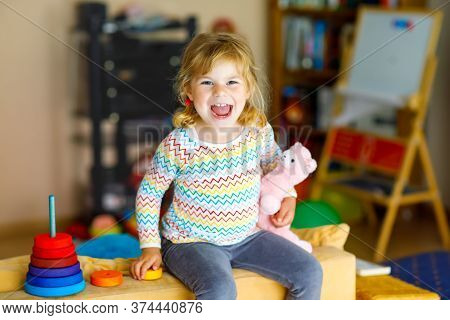 Cute Little Toddler Girl Playing Alone With Colorful Wooden Rainbow Pyramid And Toys At Home Or Nurs
