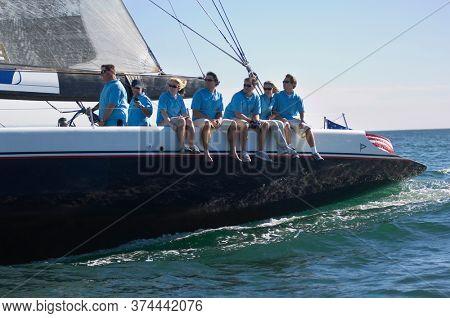 Sailing team sitting on sailboat