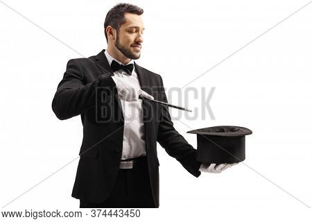 Magician performing a trick with a magic wand and a top hat isolated on white background
