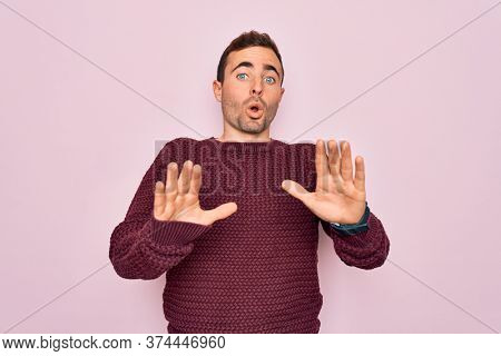 Young handsome man with blue eyes wearing casual sweater standing over pink background Moving away hands palms showing refusal and denial with afraid and disgusting expression. Stop and forbidden.