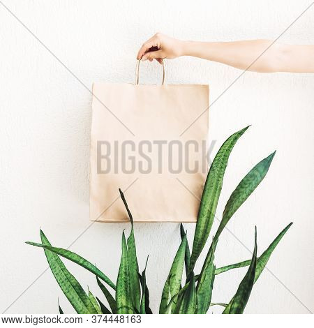 Hand Holding Craft Paper Bag For Food Or Shopping On White  Wall Background. Eco-friendly Concept Of