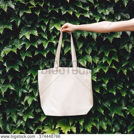 Hand Holding Craft Linen Eco Bag In The Garden Among Plants. Eco-friendly Concept Of Consumption And
