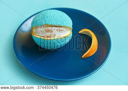 Painted Orange In Blue On A Plate. Peeled Slice Of Peel