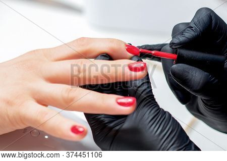 Manicurist Paints Fingernails With Red Nail Polish In Salon Close Up.