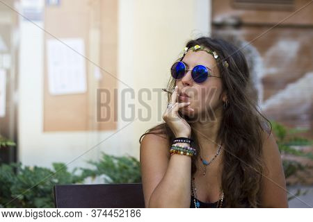 Beautiful Hippy Curly Brunette Girl Smoking Weed And Wearing Round Retro Blue Sunglasses. Woman With