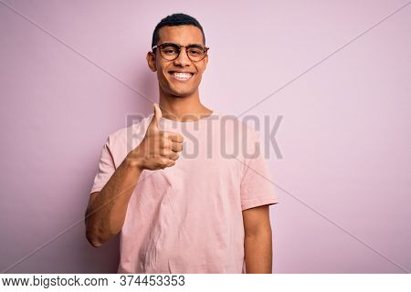 Handsome african american man wearing casual t-shirt and glasses over pink background doing happy thumbs up gesture with hand. Approving expression looking at the camera showing success.