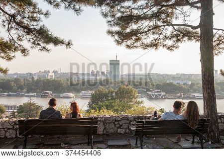 Belgrade, Serbia - July 11, 2018: Two Couples Of Lovers Sitting On Benches Observing New Belgrade (n