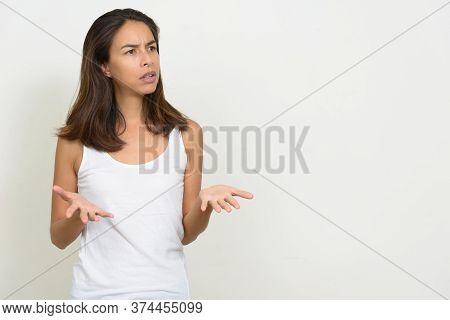Portrait Of Stressed Multi Ethnic Woman Shrugging Shoulders