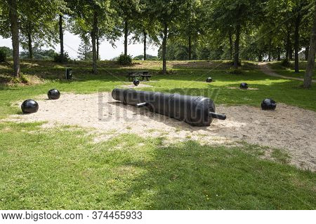 The Barrel Of A Cannon With Cannon Balls Around It