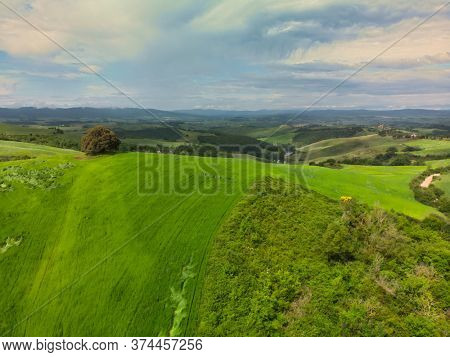 Amazing colorful sunset in Tuscany. Picturesque agrotourism and typical curved road with cypress, landscape in Tuscany, Italy, Europe
