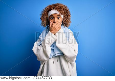 Young african american sportswoman doing sport wearing sportswear and towel shocked covering mouth with hands for mistake. Secret concept.