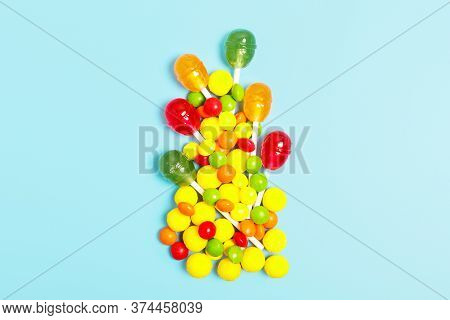 Multicolored Sweets, Candies And Lollipops On A Blue Background. Sweets Store Concept. Concept Unhea