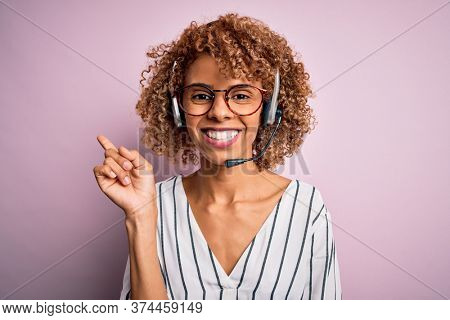 African american curly call center agent woman working using headset over pink background with a big smile on face, pointing with hand and finger to the side looking at the camera.