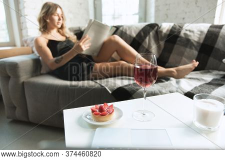 Focus On Wine Glass. Portrait Of Pretty Young Girl In Modern Apartment In The Morning. Resting, Calm