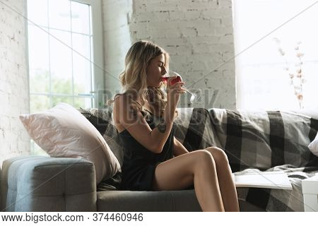 Drinking Wine, Reading Magazine. Portrait Of Pretty Young Girl In Modern Apartment In The Morning. R