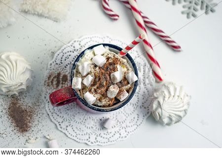 Hot Cocoa In A Red Mug With Marshmallows And Whipped Cream On A White Background, Near Sugar Canes,