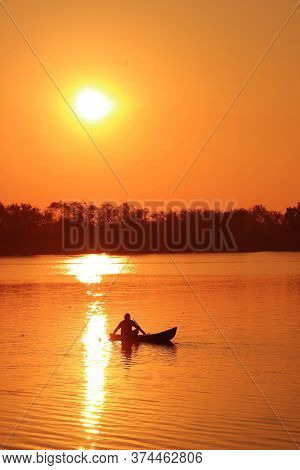 Vertical Image Of A Silhouette Of Fisherman Working On The Boat On The Lake In Late Afternoon
