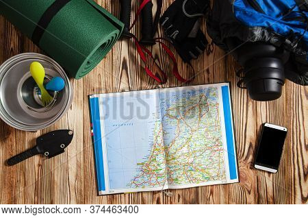 Backpack, Quad, Sticks For Scandinavian Walking And Tourist Utensils Stand On A Wooden Background