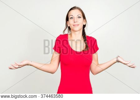 Portrait Of Confused Young Beautiful Woman With Brown Hair Shrugging Shoulders