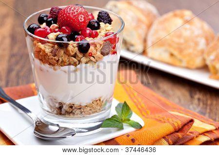 yogurt with muesli and berries in small glass