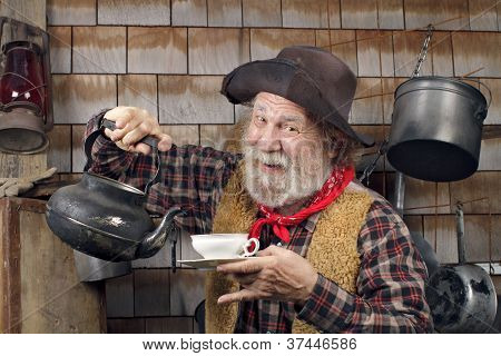 Cheerful Old Cowboy With Kettle And China Tea Cup