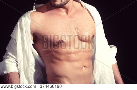 Close-up Of A Perfect Abs With Drops Of Water. Athletic Guy In White Shirt.